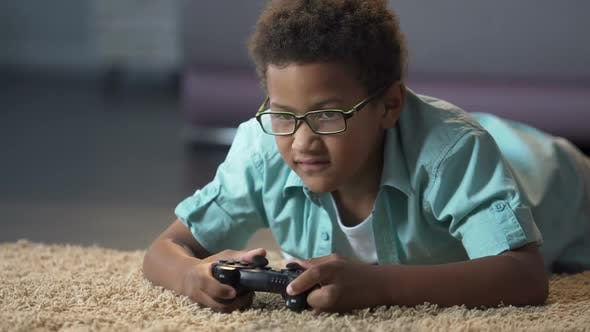 Cover Image for Afro-American Boy Absorbedly Playing on New Video Game Console Activity