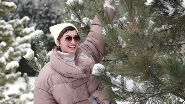 Beautiful Woman in Winter Warm Clothes and Glasses Near the Snowcovered Fir Trees