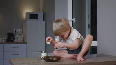 Little Boy Sits on Table and Break an Egg Into Plate