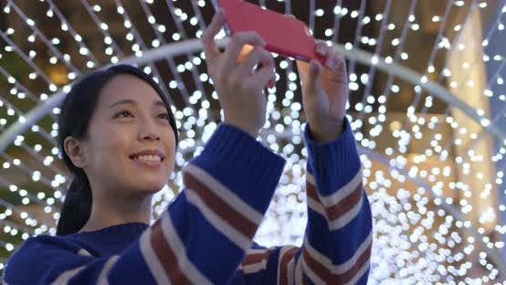 Thumbnail for Woman use of the phone for take photo with the christmas decoration at night