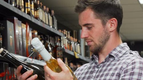 Young Man Looking Confused While Choosing Wine