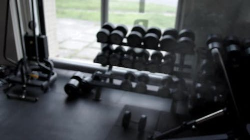 A man in a gym rubbing chalk over his hands with cotton and takes a barbell in his hands