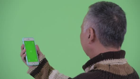 Thumbnail for Closeup Rear View of Happy Mature Japanese Man Using Phone