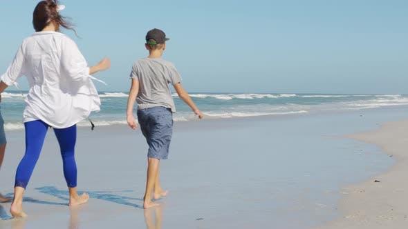 Glückliche Familie spielt und Spaß am Strand hat