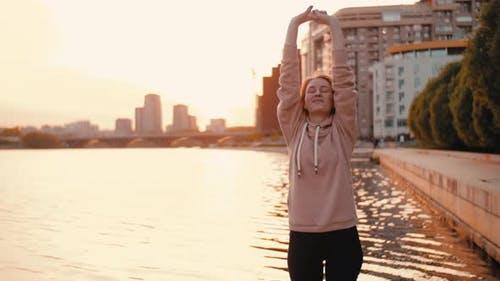 Fit Woman Stretching Upper Body Before Running in City Streets in Summer Sunny Morning