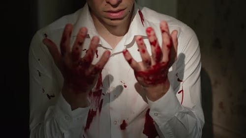 Scared Man Looks at His Bloody Hands