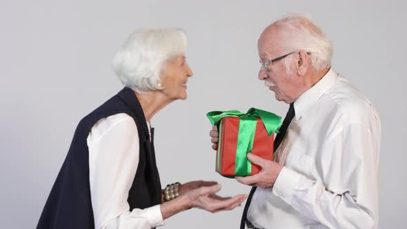 Cover Image for Elderly Woman Giving Present to Senior Man