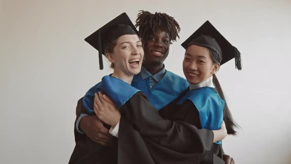 Multi-Ethnic Graduate Students Hugging on Camera