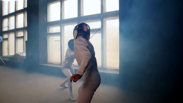 Thumbnail for Two Young Women Fencers Having a Training Duel in the Smoky Studio