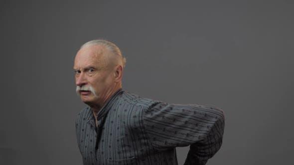 Thumbnail for Sad Senior Man Grabs Back Looks at Camera and Shakes Head