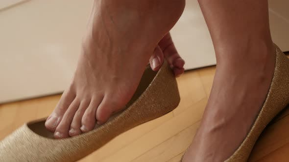 Thumbnail for Elegant evening shoes try-out  4K 2160p 30fps UltraHD  footage - Woman tries  golden color ballet fl