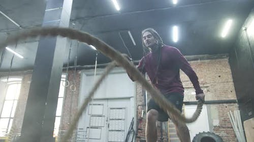 An Athletic Man is Exercising with Sports Ropes