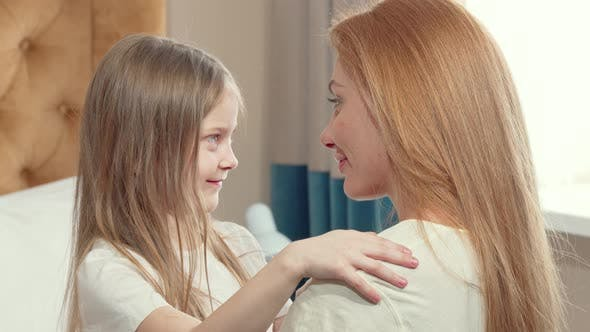 Thumbnail for Little Girl Hugging Her Mother with Her Eyes Closed