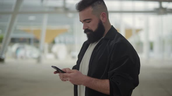 Thumbnail for Focused Young Bearded Man Using Smartphone