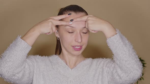 Positive Female Vlogger Doing Face Lifting Exercises on Forehead, Blogging