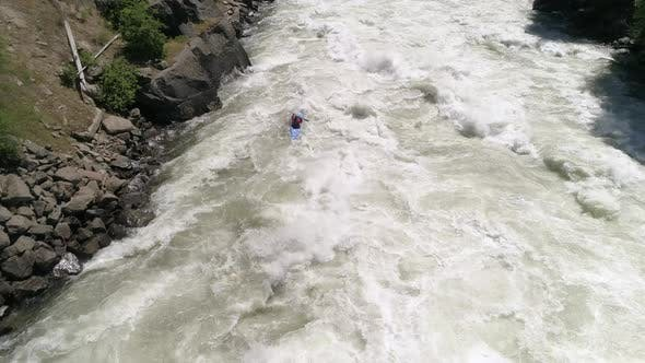 Thumbnail for Aerial Of Extreme White Water Kayaking Following Paddler Down Raging River With Violent Rapids