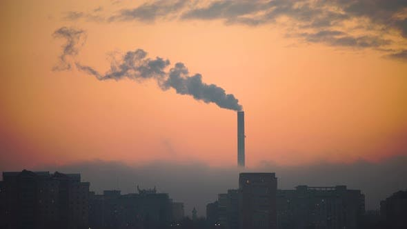 Industrial Refinery Tower with Building Silhouette in the City at Sunset