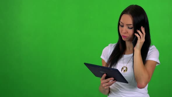 Cover Image for Young Pretty Woman Works on Tablet and Phone with Smartphone - Green Screen - Studio