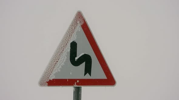 Highway Sign of Mountain Winding Road in Heavy Snowfall Weather