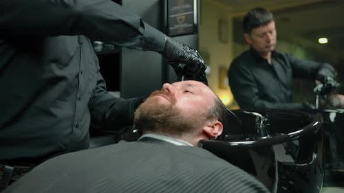 Bearded Man Washed with Shampoo Foam in a Barbershop By Professional Barber