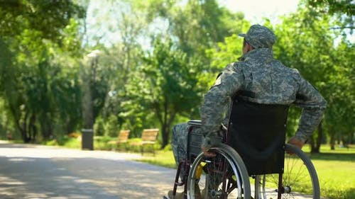 Injured Soldier in Wheelchair Moving in Park, Social Military Support, Pension