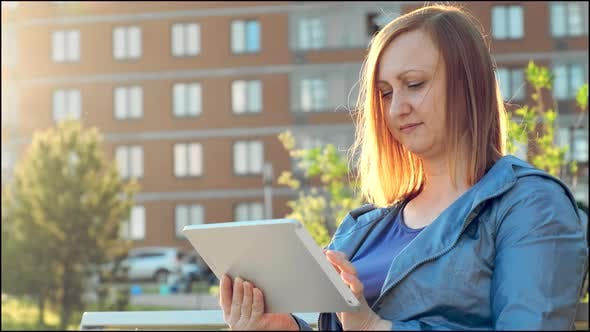Woman Using Tablet Computer Sitting on Bench in City