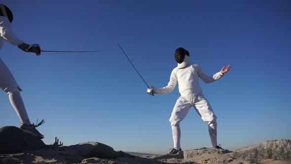 Thumbnail for A man and woman fencing on the beach.