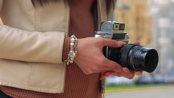 Thumbnail for An Asian Woman Holds a Camera - Closeup - an Urban Area in the Blurry Background