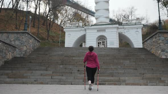 Thumbnail for Young chubby attractive female going up the stairs with poles for nordic walking. Weight loss