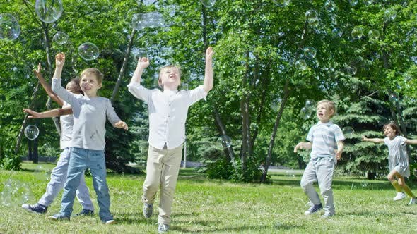 Thumbnail for Happy Children Chasing Soap Bubbles at Outdoor Party