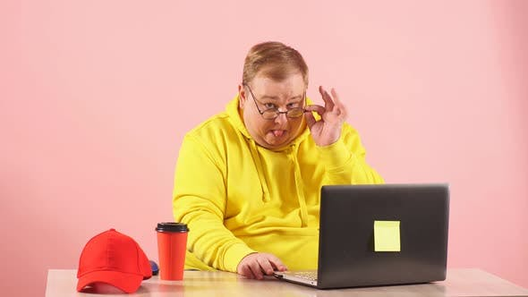 Funny Plump Man in Yellow Sweatshirt Using Laptop with Funny Freak Grimace