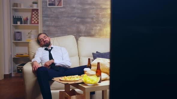 Young Businessman in Suit Falling Asleep on the Couch