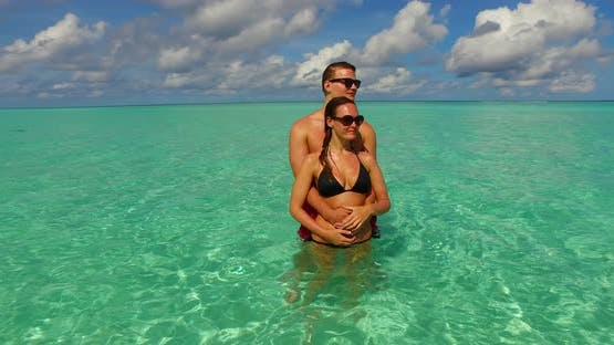Young people in love dating on vacation enjoy luxury on beach on sunny white sandy 4K background