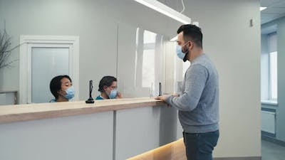 Man in Mask Speaking with Nurse on Hospital Reception