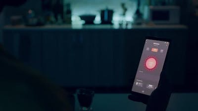 Person Looking at Smartphone with Lights Controlling Software
