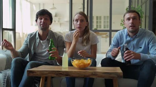 Funny Friends Celebrate the Victory of Their Favorite Team Sitting on the Couch