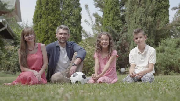 Thumbnail for Happy Family Sitting on the Grass in the Garden Together. Mother, Father, Son, and Daughter Looking