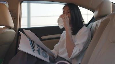 young Asia businesswoman working and drinking disposable paper cup of hot drink in back seat.