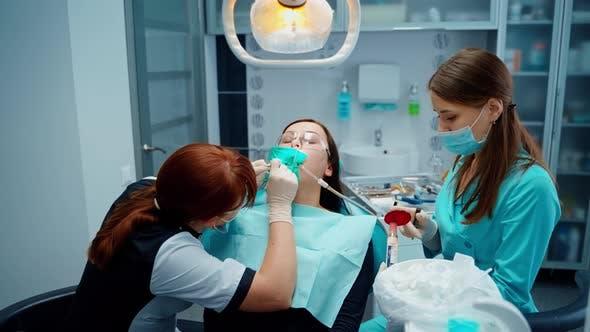 Female dentist treating teeth to female patient