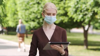 A Woman in a Medical Mask Stands in the Middle of the Street and Scrolls a Tablet