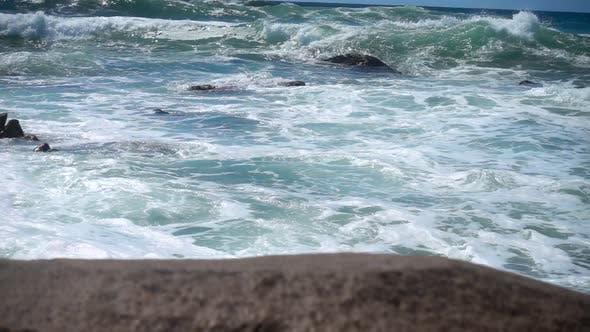 Static Cinematic Shot of Blue Sea Waves Crashing on Rocks