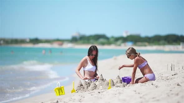 Thumbnail for Family of Mom and Girl Making Sand Castle at Tropical White Beach