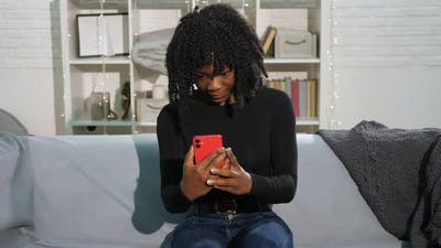 African American Lady with Curly Hair Types on Smartphone