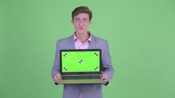 Cover Image for Happy Young Businessman Showing Laptop and Looking Surprised