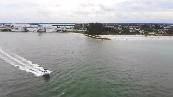 Luftbild-Motorboot, das schnell auf dem Meer in der Nähe der Küste, des bewölkten Tages und der Meeresküste segelt