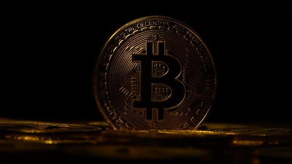 Thumbnail for Bitcoins drehen sich in einem Kreis im Dunkeln auf schwarzem Hintergrund. Nahaufnahme