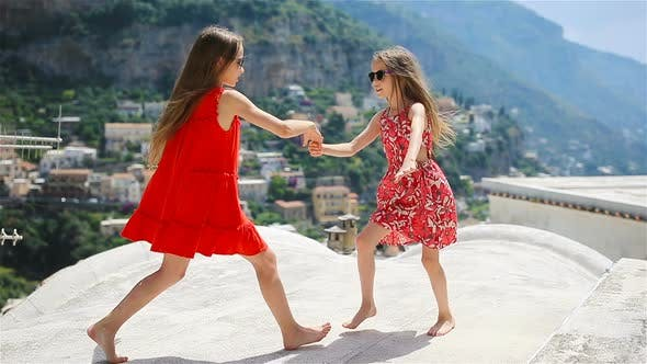 Adorable Little Girls on Warm and Sunny Summer Day in Positano Town in Italy