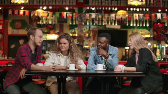 Thumbnail for Four People in a Coffee Shop Are Talking and Smiling, Multi-ethnic Couples