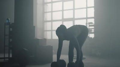 Sportswoman Exercising with Heavy Dumbbells