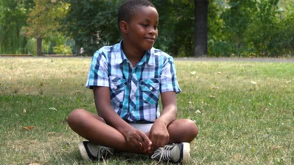 Thumbnail for A Young  Black Boy Sits on Grass in a Park and Dances with a Smile